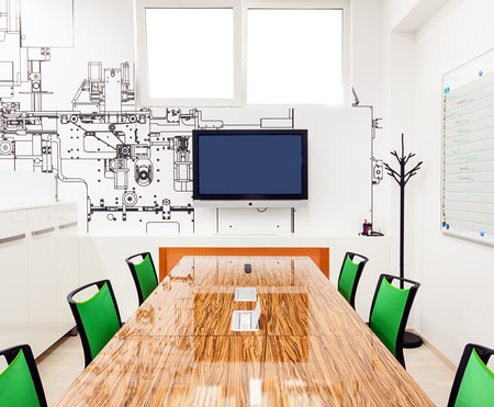 class maintenance: Office interior in white with printed wallpapers presenting part of a machine structure.