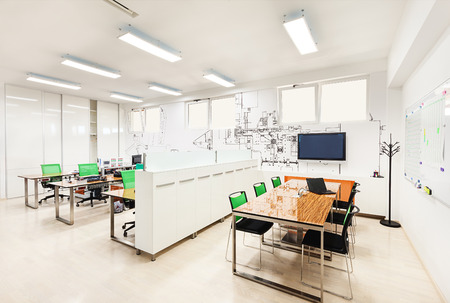 Office interior in white with printed wallpapers presenting part of a machine structure.