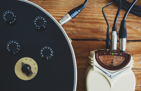 solid wire: Details of an old guitar tuner, solid built with dust on surface, turned on.