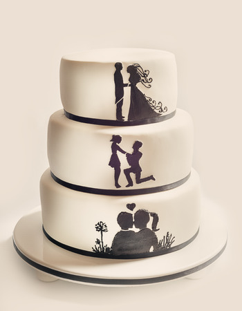 wedding love: Details of a wedding cake, white sugar cream and black silhouettes. Stock Photo