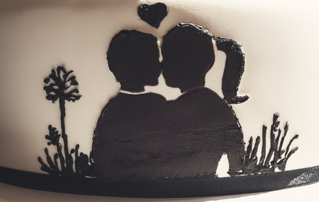 love affair: Details of a wedding cake, white sugar cream and black silhouettes. Stock Photo