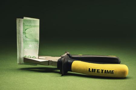 dinero euros: Composición conceptual presentar alicates dinero refieren sostiene un billete de ? 100 con el título de por vida en ella.