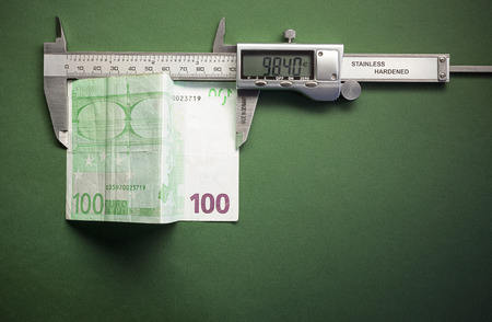 showed: Conceptual composition representing money devaluation symbolically showed with sliding calliper measuring a hundred euros.