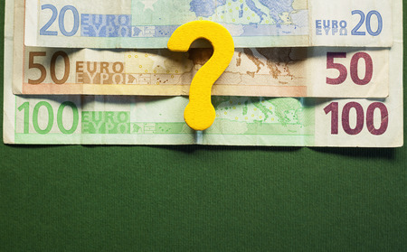 upper half: Conceptual image about euro devaluation euro banknotes in upper half empty down half green background.