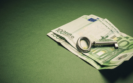 Conceptual composition euro hundred banknotes with key as symbolic object. photo