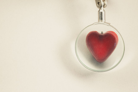 showed: Symbolically showed examination of a heart souvenir in shape of heart viewed through magnifier.