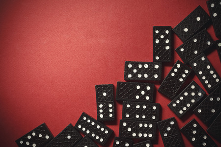 dominoes: Background composition with black plastic dominoes on one side and empty part on other side.
