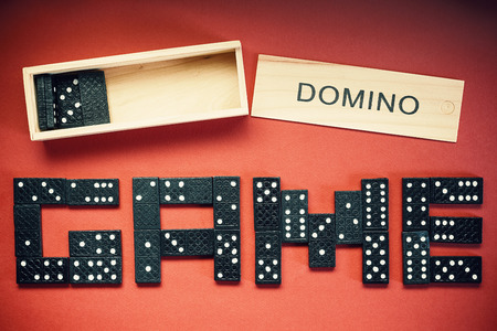 word game: Word game written of dominoes on red background.