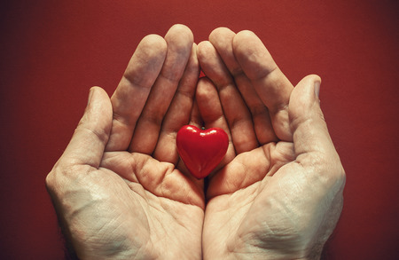 meaning: Two male hands holding red wooden heart conceptual composition about love. Stock Photo