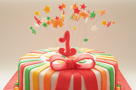 1st: Details of decoration of first year birthday cake focus on number one. Stock Photo