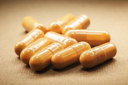 diagnoses: Macro view of yellow pills, blurry background.