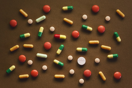 diagnoses: Various pills and tablets on brown textured background. Abstract composition. Stock Photo