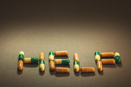 diagnoses: Word help written with pills, blurry brown background. Stock Photo