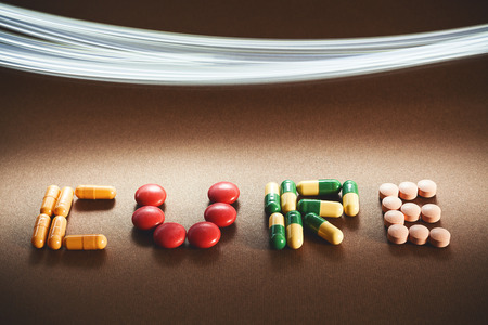 diagnoses: Word cure written with various different pills and tablets, lighting effect in upper side of image. Stock Photo