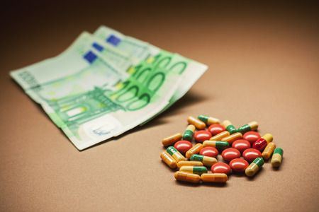 diagnoses: Conceptual composition representing a need for cure, euro banknotes in blurry background.
