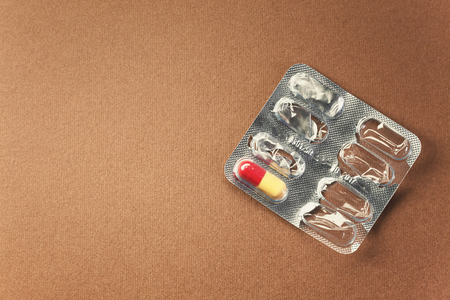 symbolically: Conceptual composition, empty pills pack with just one left, symbolically represents last chance, or simple a cure, the need and similar. Stock Photo