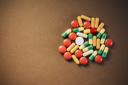 diagnoses: Bunch of various colorful unpacked pills and tablets, on brown textured background, with empty space on left side of an image. Stock Photo
