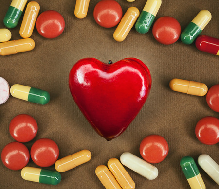 diagnoses: Conceptual composition about heart sickness, various colorful pills around souvenir in shape of heart as symbol.