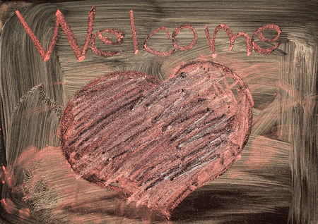 symbolically: Word welcome and shape of heart written with chalk on dirty black board.