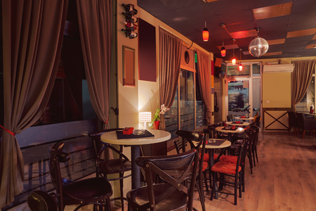 room decor: Interior of a modern cafe in retro style, night scene. Illumination, furniture and architectural details.