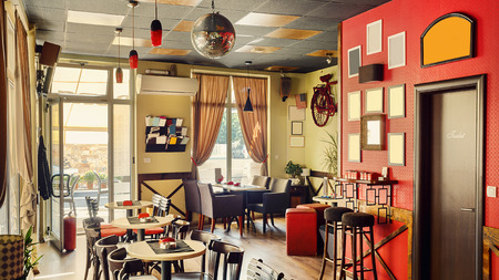 interior architecture: Interior of a modern cafe in retro style, during day. Furniture and architectural details.