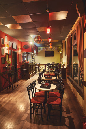 Interior of a modern cafe in retro style, night scene. Illumination, furniture and architectural details.