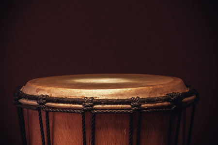 Details of an old wooden djembe, closeup view on ropes, skin and wood. Stock Photo
