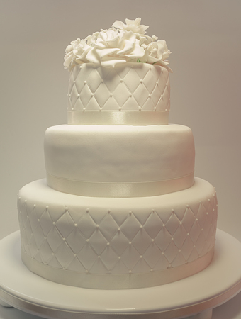wedding cake: Details of a wedding cake, decoration with white fondant on white background.