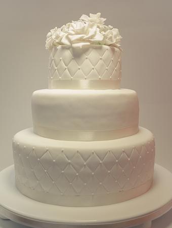 Detalles de un pastel de bodas, decoración con fondant blanco sobre fondo blanco. Foto de archivo