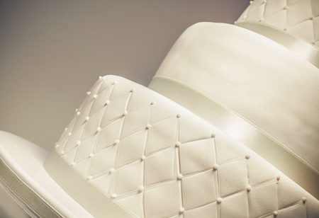 specialty: Details of a wedding cake, decoration with white fondant on white background.