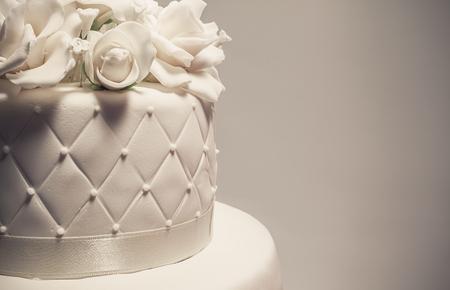 huwelijk: Details van een bruidstaart, decoratie met witte fondant op een witte achtergrond.