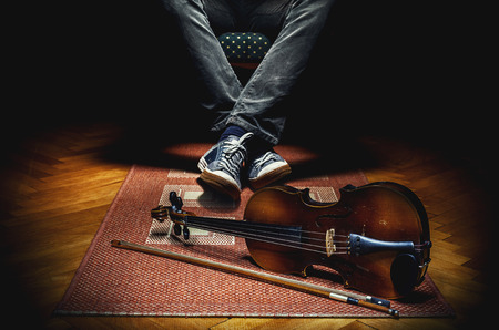 violin player: Violin player resting in armchair and his violin on tiled carpet.