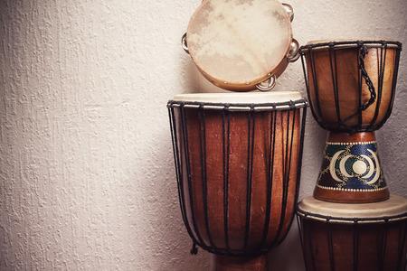 instrumentos de musica: Varios Djembés y pandereta frente a una pared rústica.