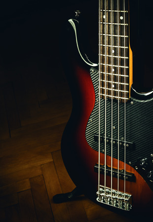 frets: Details of a five strings bass on parquet, classical jazz design.