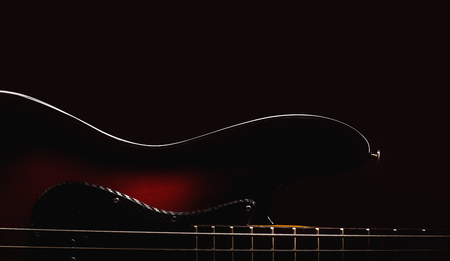 frets: Part of a jazz bass guitar, accentuated shapes with illumination. Stock Photo