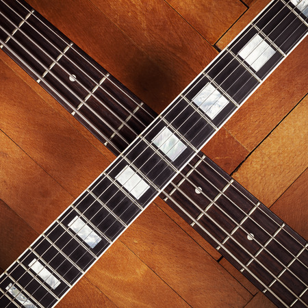 frets: Necks of electric and bass guitars on parquet.