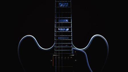 Body and neck of electric eguitar, accentuated shapes by illumination.