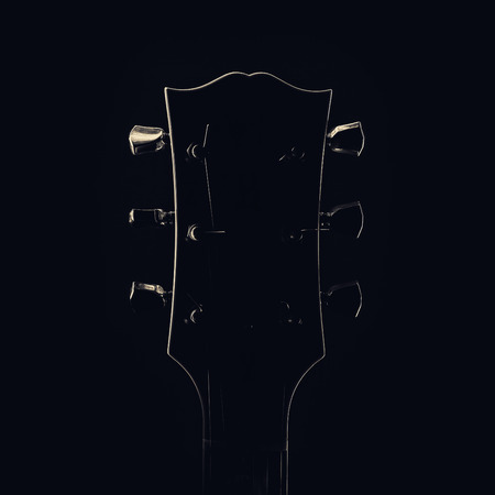 frets: Head and Neck of electric guitar, shapes accentuated by light. Stock Photo