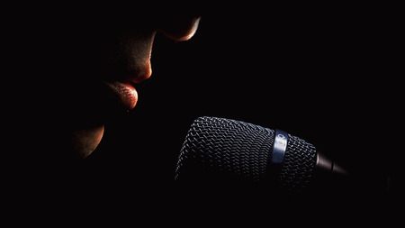 Part of a singer face, details of mouth and modern black microphone, on black background. Stock Photo