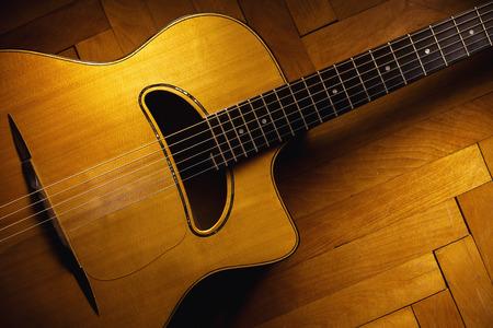 gitana: Guitarra acústica vieja gitana en el piso de parquet.