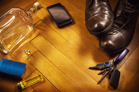 side keys: Conceptual composition about resting and enjoying home life, old retro styled leather shoes and car keys on one side and empty spirit bottle on the other.