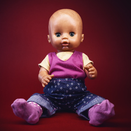 clothed: Used clothed baby toy on dark red background, portrait details.