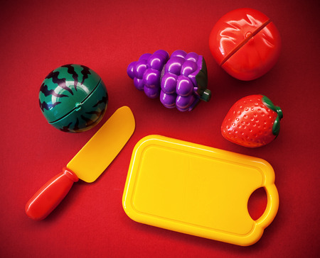 warm things: Plastic fruits and vegetables as toys, on red background.