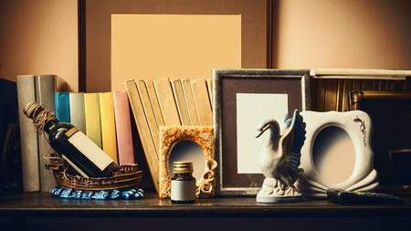 statue: Old shelf With books, souvenirs and empty photo frames. Stock Photo
