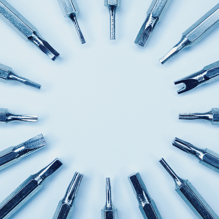 adequate: Various screwdriver heads, abstract composition with accent to differences and metal material, blue illumination. Stock Photo