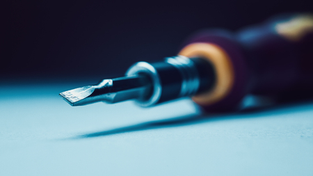 adequate: Closeup view of screwdriver, focus on head, blurry background.