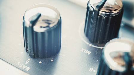 eq: Details of an old but modern, dusty and used guitar pedal, focus on buttons and eq marks.