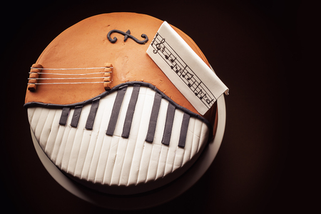 chocolate cake: Birthday cake decorated with fondant, rounded, symbolically presenting piano and cello instruments.