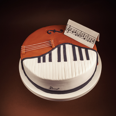 cello: Birthday cake decorated with fondant, rounded, symbolically presenting piano and cello instruments.