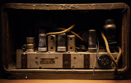 radio unit: Old tubes and electric parts of an old dusty amplifier. Stock Photo